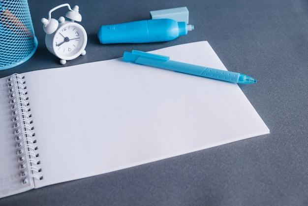 空白のノートブック紙ペン蛍光ペン消しゴムと時計