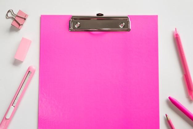 ピンクのクリップボードと基本的な文房具