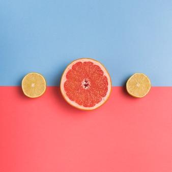 カラフルな背景に柑橘系の果物をカットします。