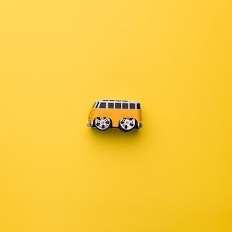 オレンジ色の背景上のおもちゃのバス