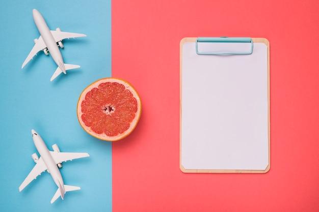 飛行機グレープフルーツと白いスケッチボードの組成
