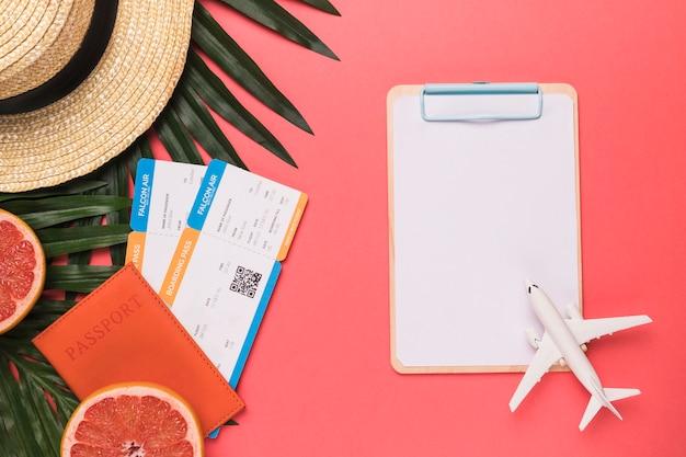 パスポートチケットのおもちゃの飛行機のスケッチボードの果物と帽子