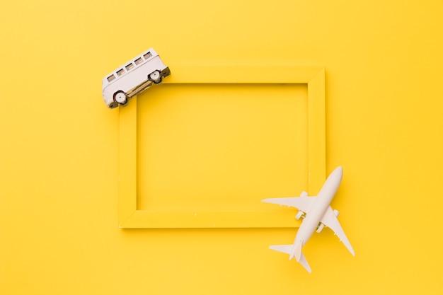 Композиция из игрушечного самолета и автобуса на желтой рамке