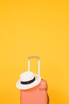 オレンジ色のスーツケースと白い帽子