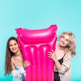 明るいピンクのプールエアーマットを持つ女性