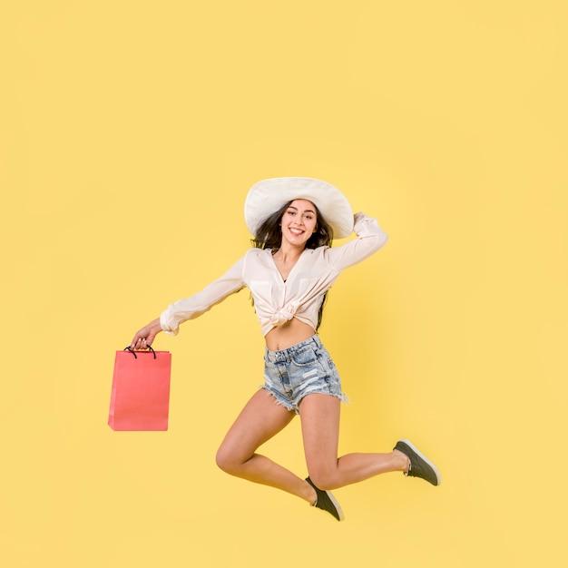 赤い紙の袋を持つ幸せなジャンプ女