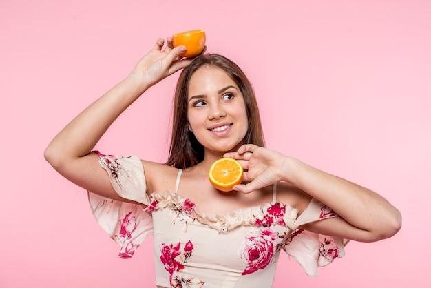 笑顔とスライスされたオレンジを楽しんでいる女性