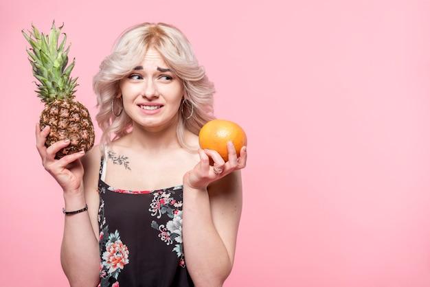 パイナップルとオレンジの手の中の選択を作る巻き毛の美しい女性
