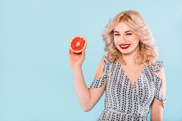 グレープフルーツの半分を持つ女性の笑みを浮かべてください。