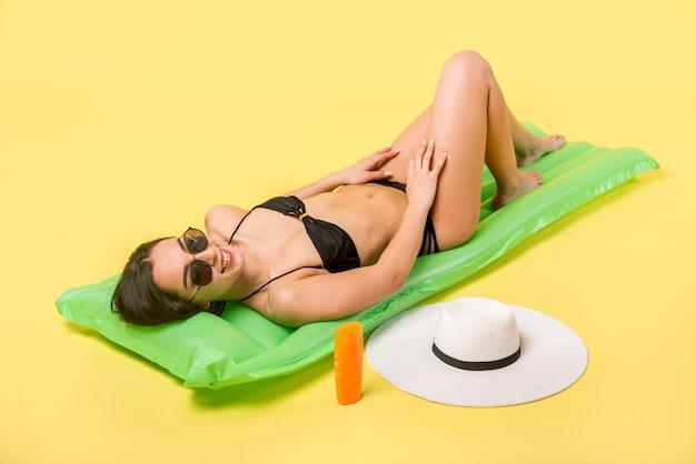 膨脹可能なマットレスの上に横たわる美しい女性