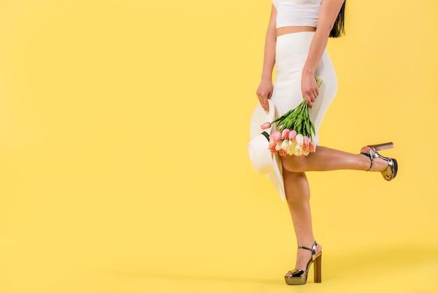 チューリップの花束を持つファッショナブルな女性