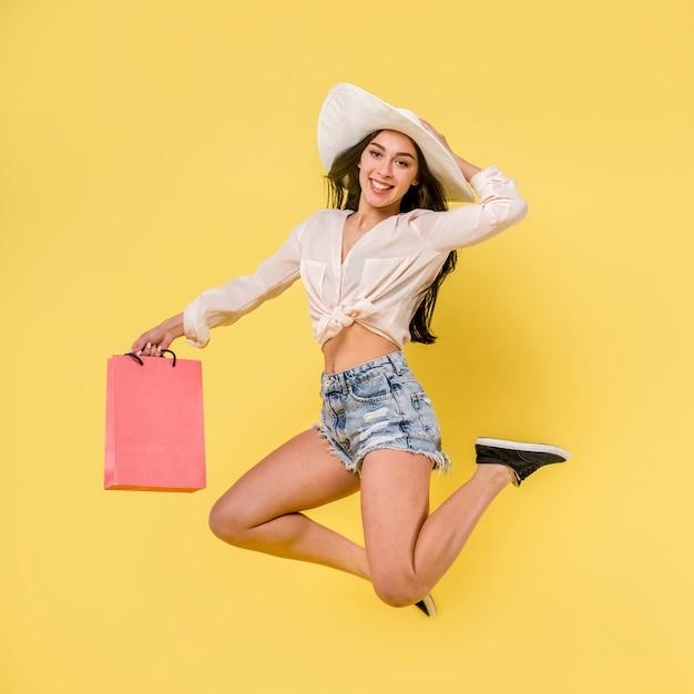Счастливая прыгающая женщина в белой шляпе