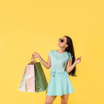 Веселая женщина стоит с сумками