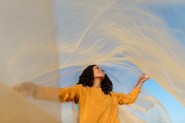 自然の中で布を保持している女性との自由の概念
