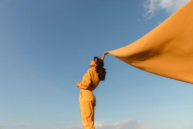 Концепция свободы с женщиной, держащей ткань в природе