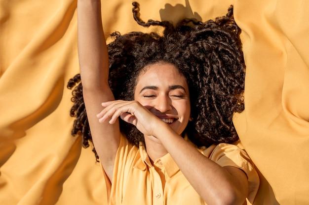自然の中で黄色い布の上に横たわる若い女性