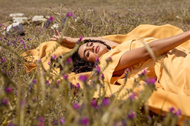 Молодая женщина, лежа на желтой ткани в природе