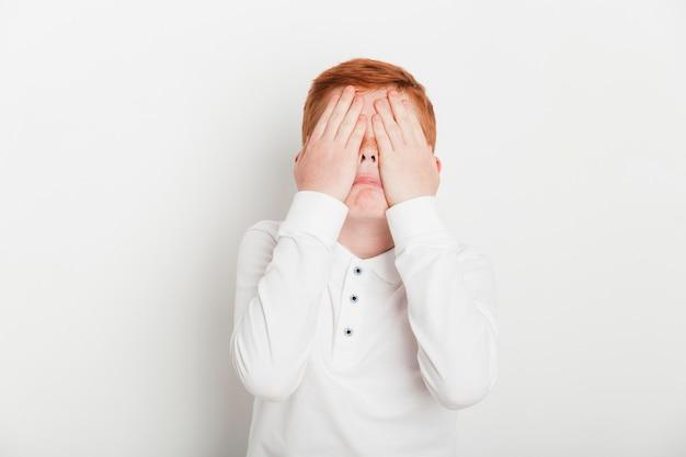 彼の目を覆っている生姜の少年