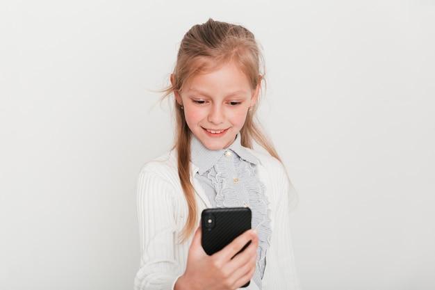 Маленькая девочка смотрит на свой смартфон
