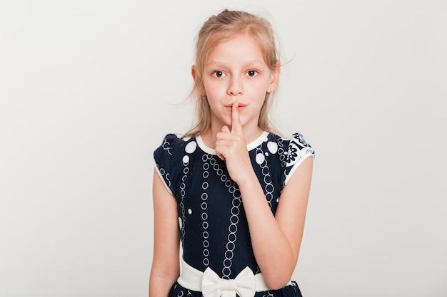 沈黙のジェスチャーを作る小さな女の子