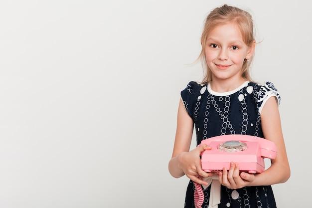 Маленькая девочка держит ретро телефон