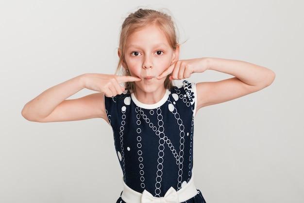 Маленькая девочка делает глупое выражение