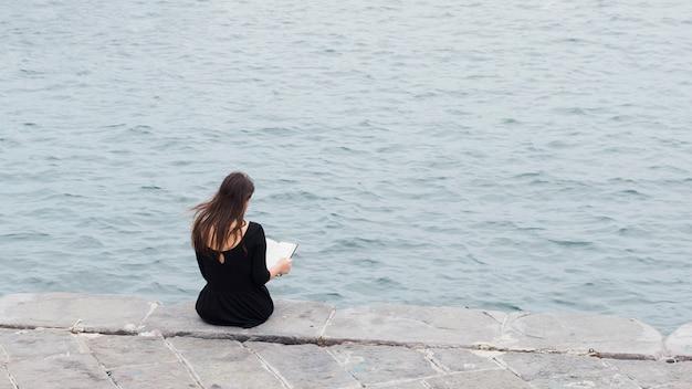 通りで本を読んでいる女の子