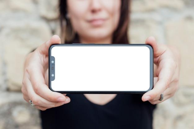 人がスマートフォンの画面を保持