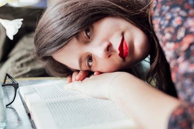 本をテーブルの上の若い女の子