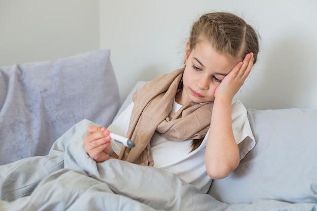 Больная девушка с помощью термометра