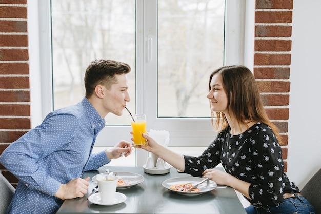 レストランでオレンジジュースを持っているカップル