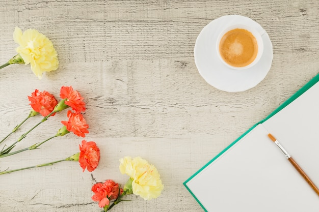 Вид сверху цветы с книгой и кофе на деревянном фоне