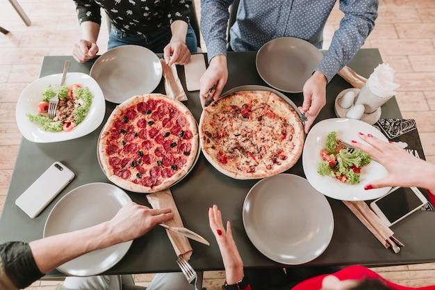Люди едят пиццу в ресторане