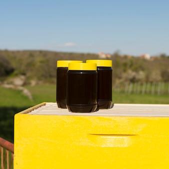 黄色いカバーが付いている蜂蜜の瓶