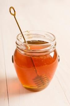 蜂蜜スプーンと蜂蜜でいっぱいのガラス瓶