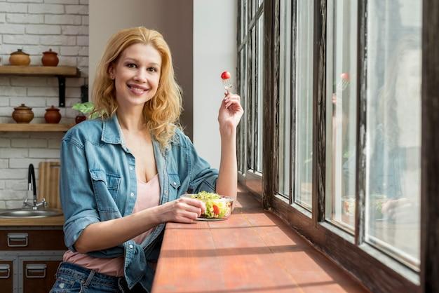 金髪の女性がサラダを食べる