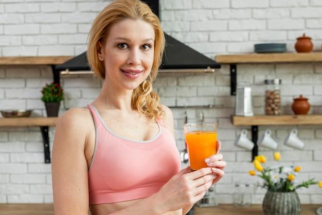 金髪の女性がオレンジジュースを飲む