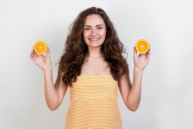 ブルネットの女性、オレンジを保持