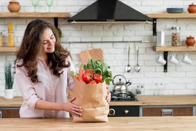 Брюнетка с бумажной сумкой, полной здоровой пищи