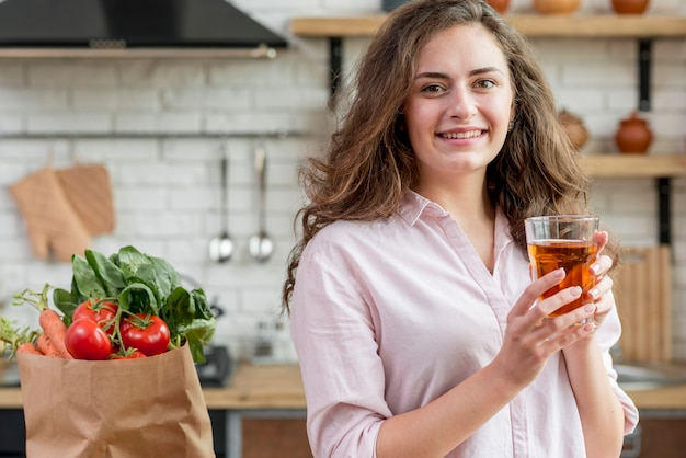 健康的な食品の完全な紙袋をブルネットの女性