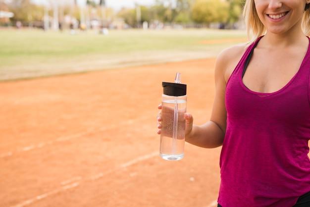 スタジアムトラック上の水のボトルを持つスポーティな女性
