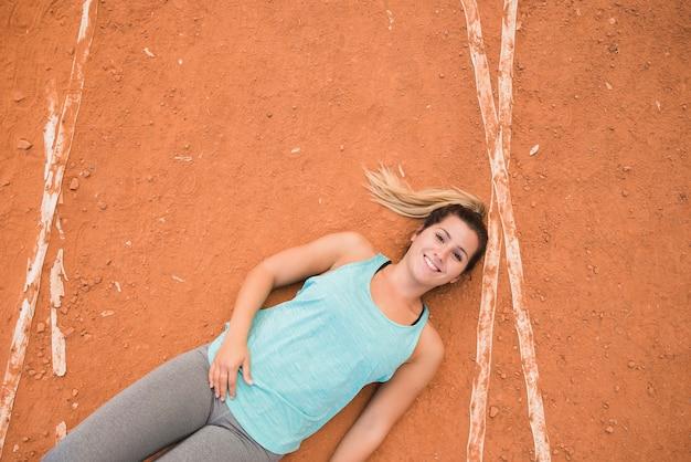 Спортивная женщина, лежа на дорожке стадиона