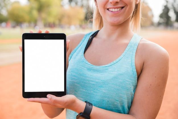 Спортивная женщина, представляя шаблон планшета