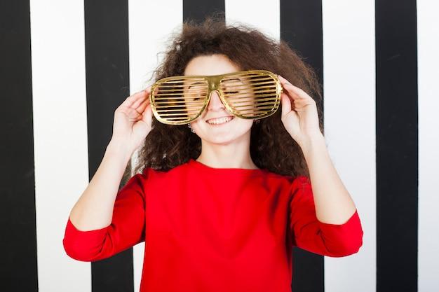 縞模様の背景に面白いブルネットの少女の肖像画
