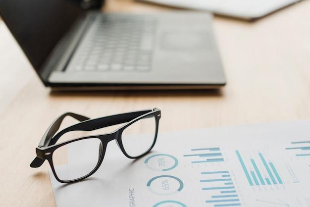Офисный рабочий стол с ноутбуком и очками