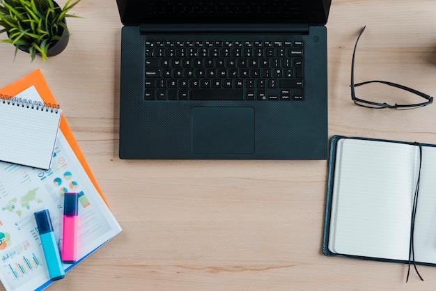 ノートパソコンとアナリティクスを備えたオフィスデスクトップ