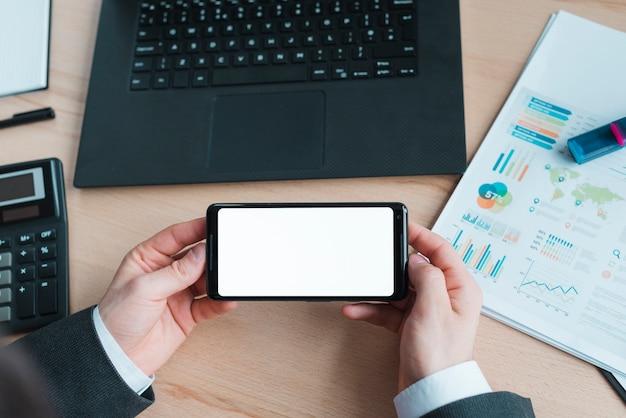 ノートパソコンと携帯電話を持つオフィスのデスクトップ