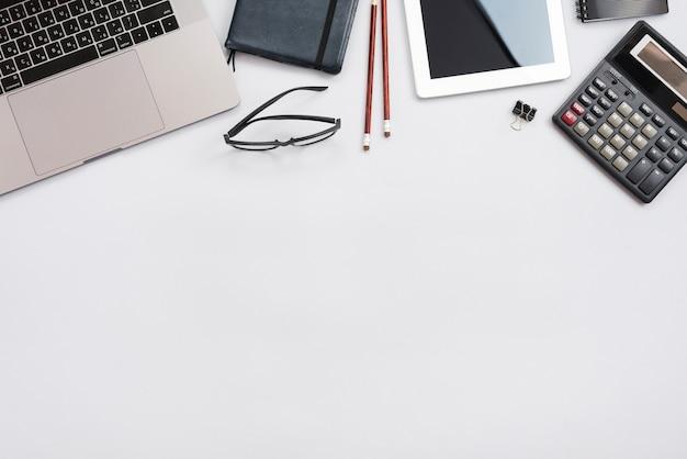 ノートパソコンと電卓とオフィスのデスクトップ