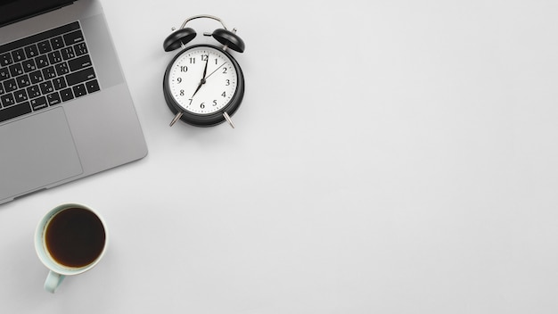 ノートパソコンと時計とオフィスのデスクトップ