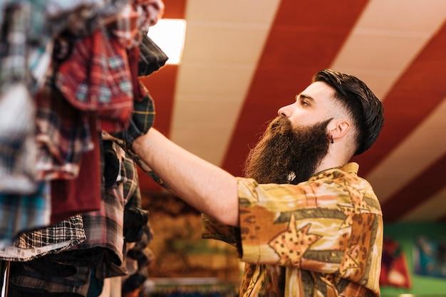 Длинный бородатый мужчина, глядя на одежду, висит на рельсе в магазине
